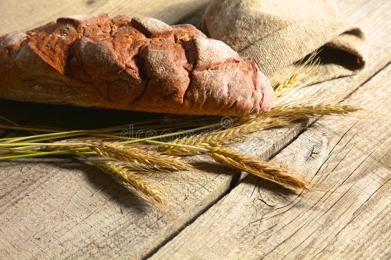 Rustic crusty bread and wheat ears on a dark wooden table.  royalty free stock photo