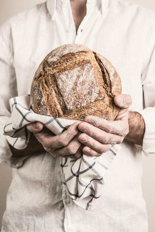 Rustic crusty loaf of bread in baker man`s hands. Rustic crusty loaf of bread in a strong baker man`s hands - closeup. Small business and slow food concept royalty free stock images