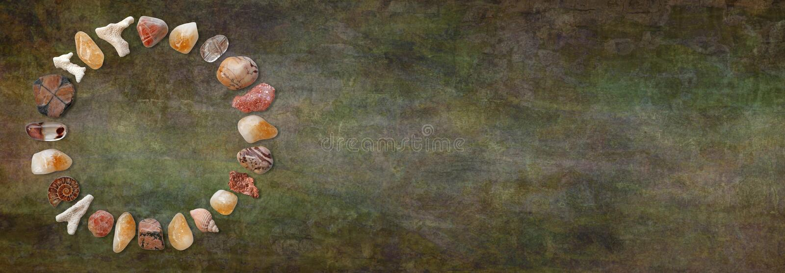 Rustic Crystal Circle Website Header. Tumbled healing crystals making a neat circular border against dark rustic stone background with copy space on right and royalty free stock photo