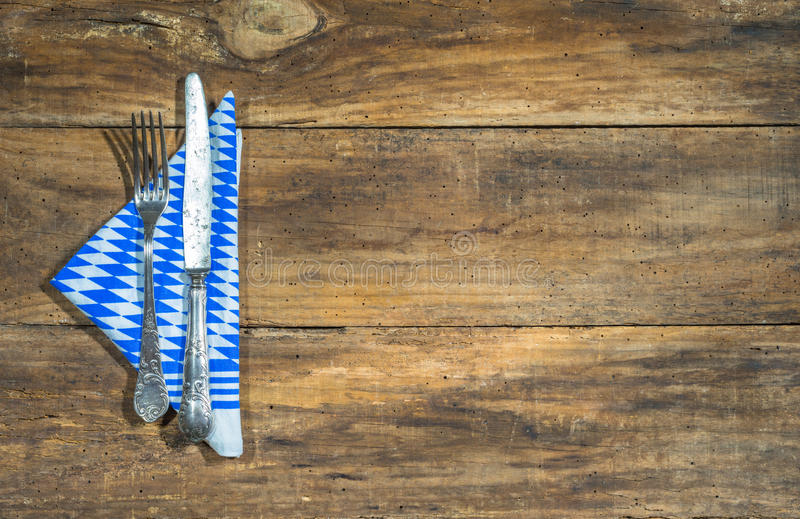 Rustic cutlery with napkin at bavarian pattern on old wooden table. stock images