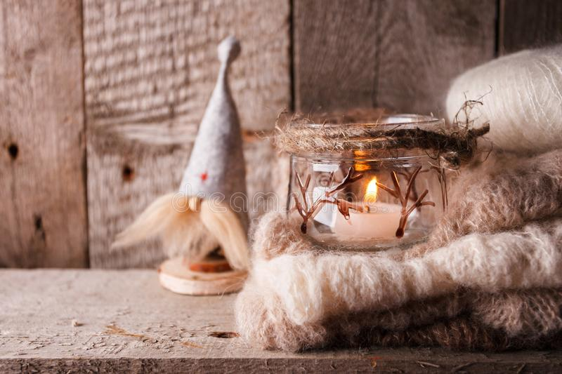 Rustic decoraton with handmade interior toy gnome, candle and warm knitted scarf on brown wooden background, perfect for scandi royalty free stock photos