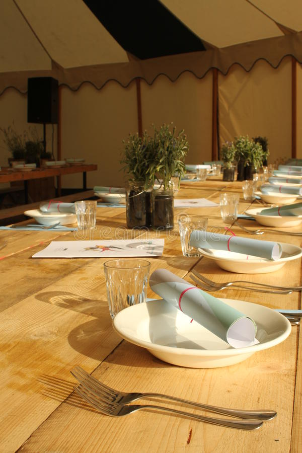 Rustic dining table. Dining in a marquee tent on wooden benches for a festival or wedding breakfast stock images