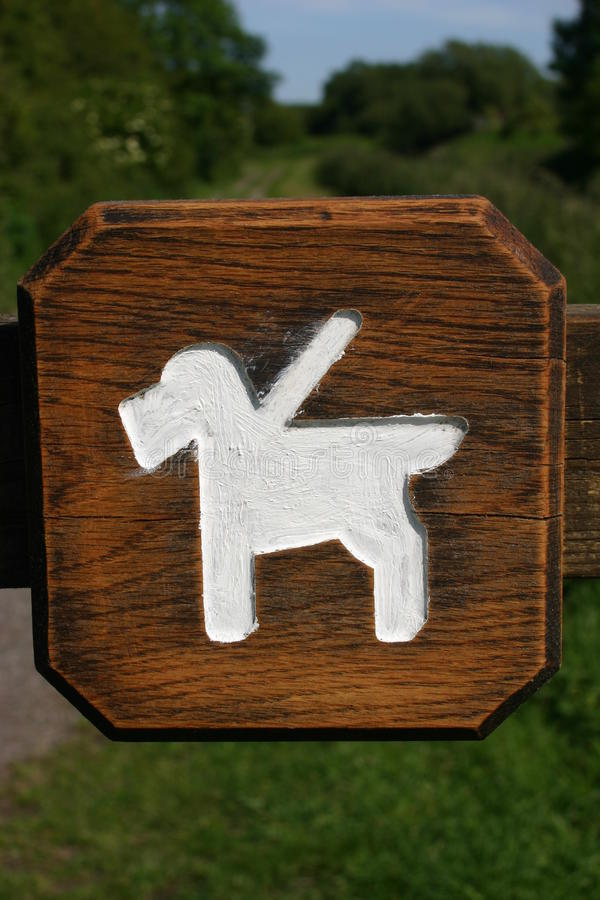Dogs on leads sign. Rustic dogs on leads sign routed into varnished wooden board with white painted dogs on lead shape royalty free stock photography