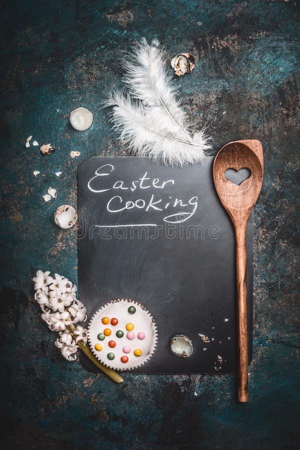 Rustic Easter cooking background with chalkboard , cake , eggs shell von quail, wooden spoon and hyacinth flower royalty free stock image