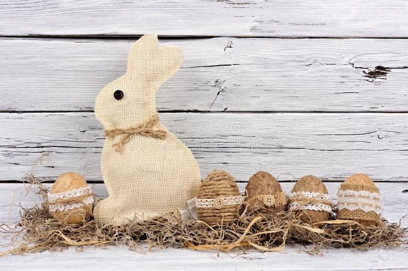 Rustic Easter eggs and bunny in moss against aged white wood royalty free stock images