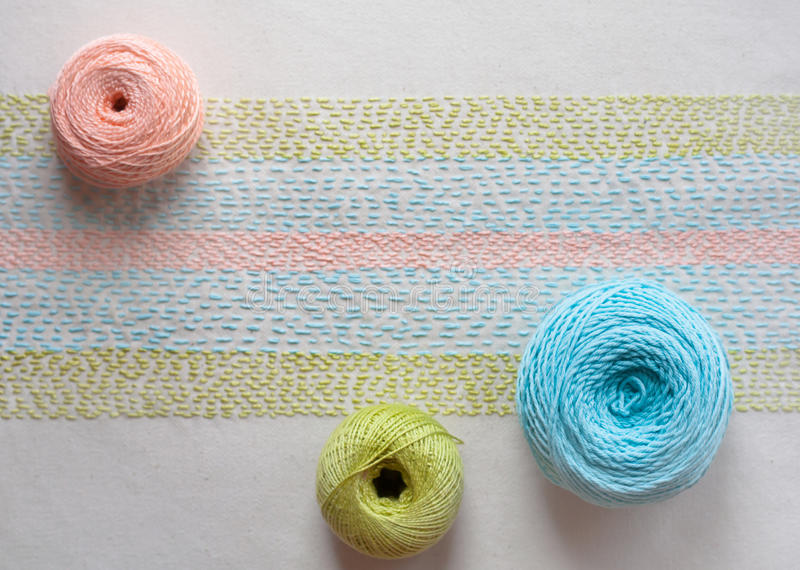 Rustic embroidery and pink, green, turquoise skeins background. stock photography