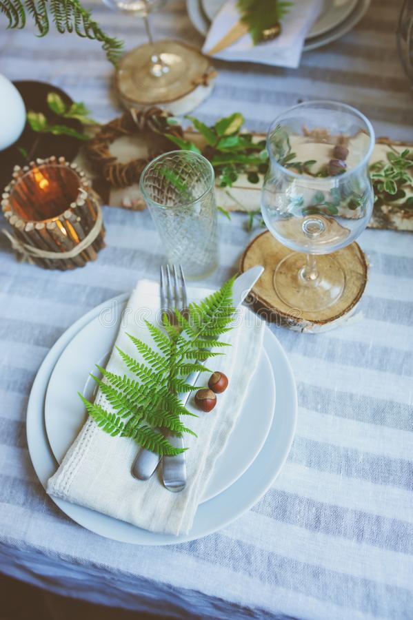Rustic festive table details with wild ferns, handmade decoration and candles. Country home dinner in summer evening stock images