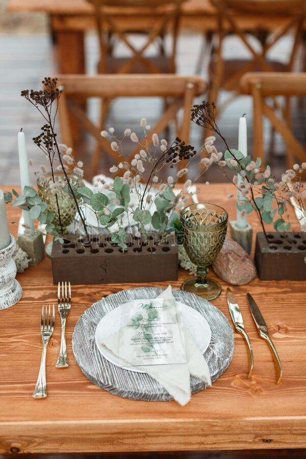 Rustic festive table setting with natural materials. On a brown wooden table is a gray wooden stand, on it is a white round plate with a textile napkin and on a royalty free stock photos