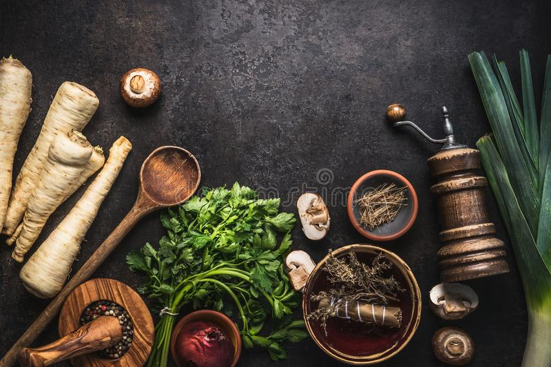 Rustic food background with parsley root vegetables, herbs,spices ,leek and champignon mushrooms on dark rustic table with kitchen stock photos