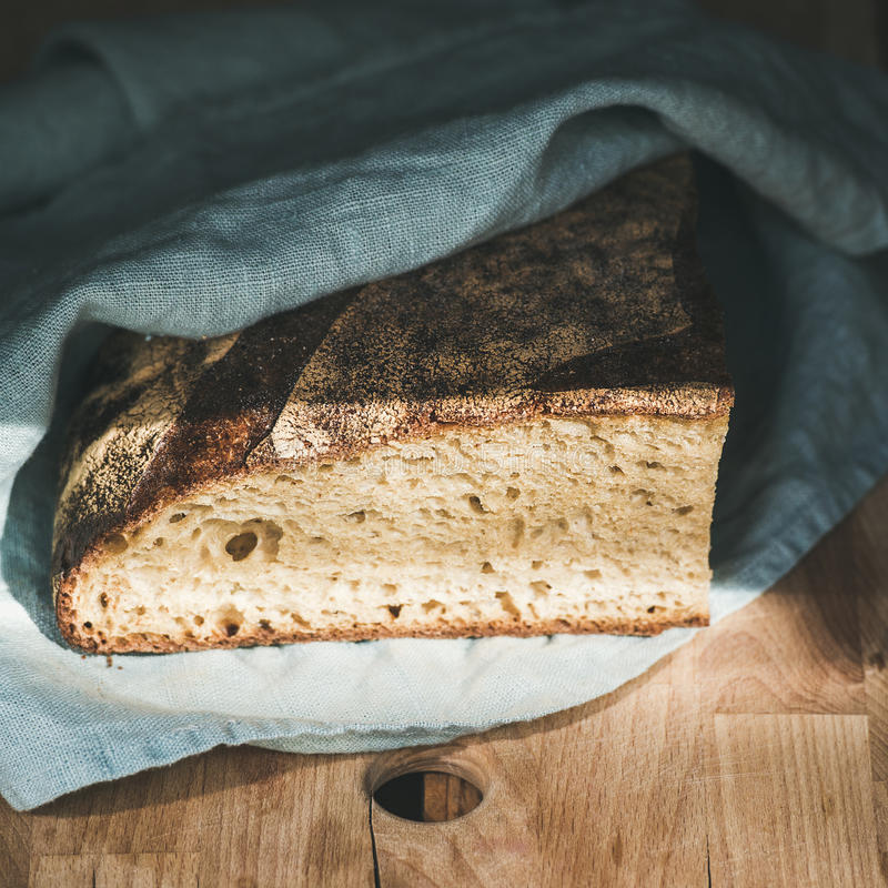 Rustic French rye bread loaf covered with kitchen towel royalty free stock photography