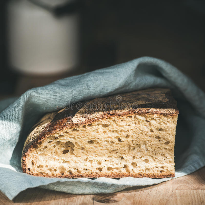 Rustic French rye bread loaf on wooden board, square crop. Rustic French rye bread loaf covered with kitchen towel over shabby wooden board, selective focus stock image