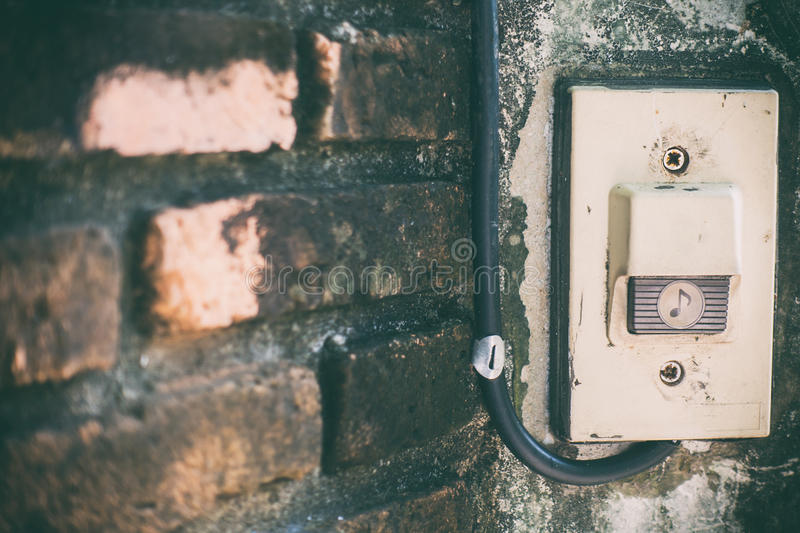 Rustic front gate door bell on brick wall stock photos