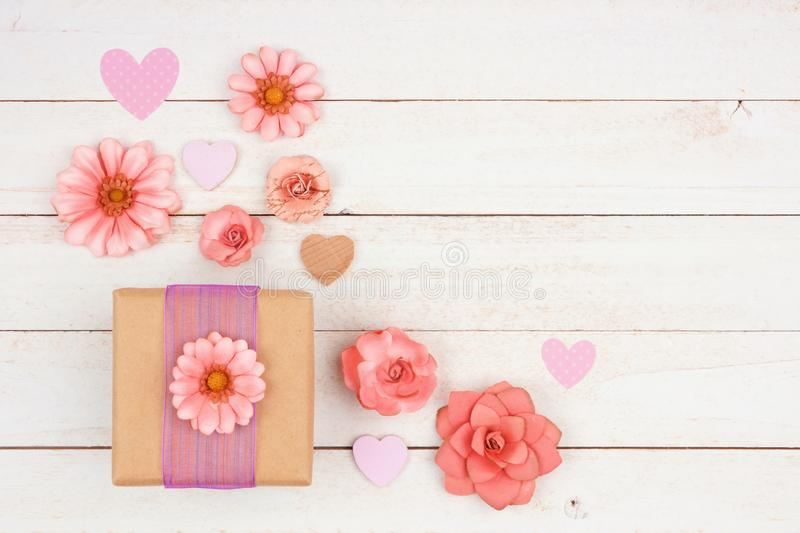Gift box with pink paper flowers and wood hearts, corner orientation against white wood stock images