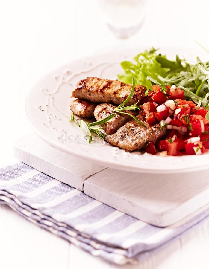 Rustic grilled pork tenderloin with tomato salsa royalty free stock photo