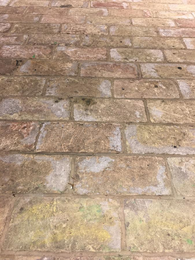 Rustic grungy urban brick wall road in brown. Pavers stock photography