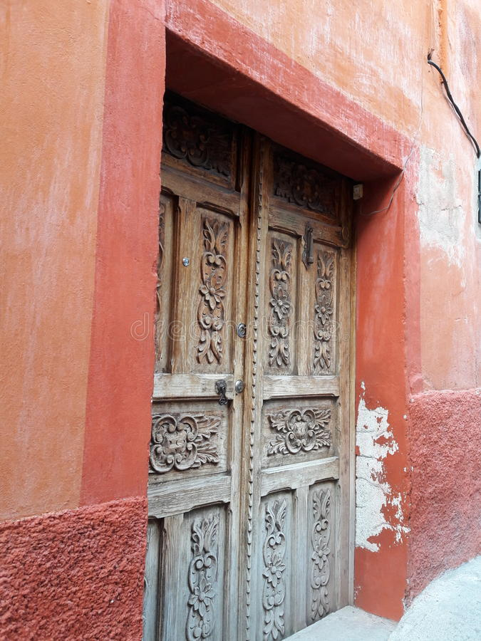 Rustic Hand-Carved Antique Wooden Door and Primitive Textured Mexican Stucco Wall in Brown, Rust and Tan Background Colors stock photos