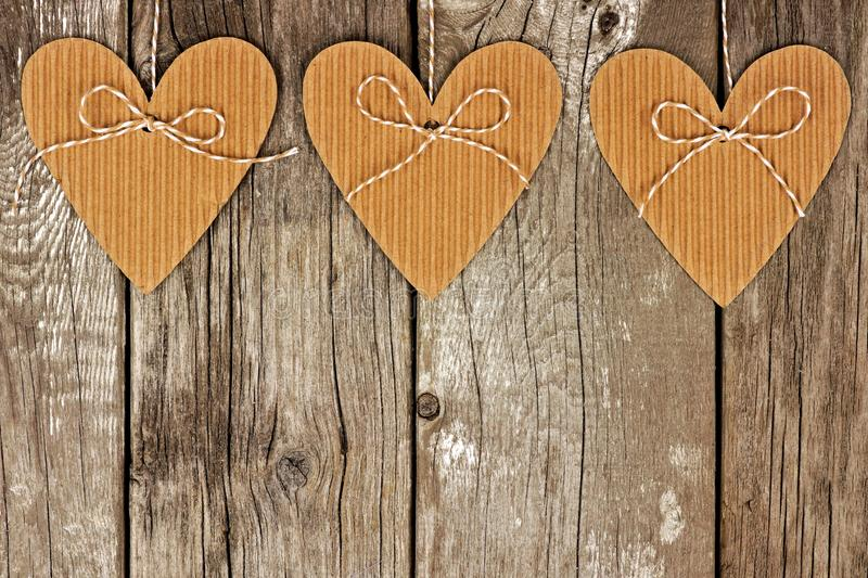 Rustic heart shaped gift tags hanging against wood. Rustic heart shaped cardboard gift tags hanging against a vintage wood background royalty free stock images
