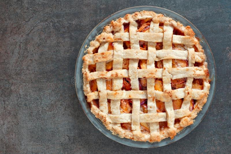 Rustic homemade peach pie, above view on stone background. Rustic homemade peach pie in baking plate, above view on a stone background stock photography