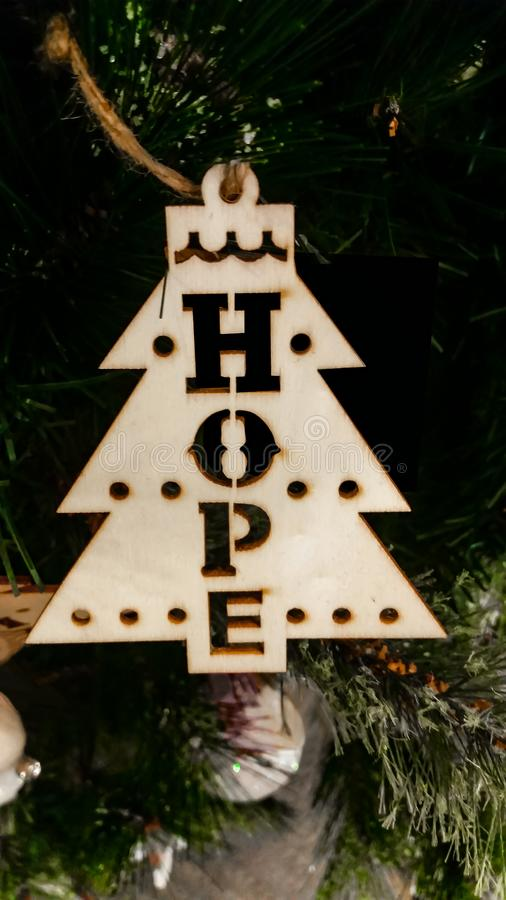 Rustic HOPE wooden Christmas ornament on rope string against a dark blurred Christmas tree stock photo