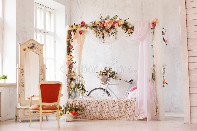 Rustic interior of the bedroom. A bed with an arch of flowers, a mirror, an armchair and a retro bicycle stands at the stock images