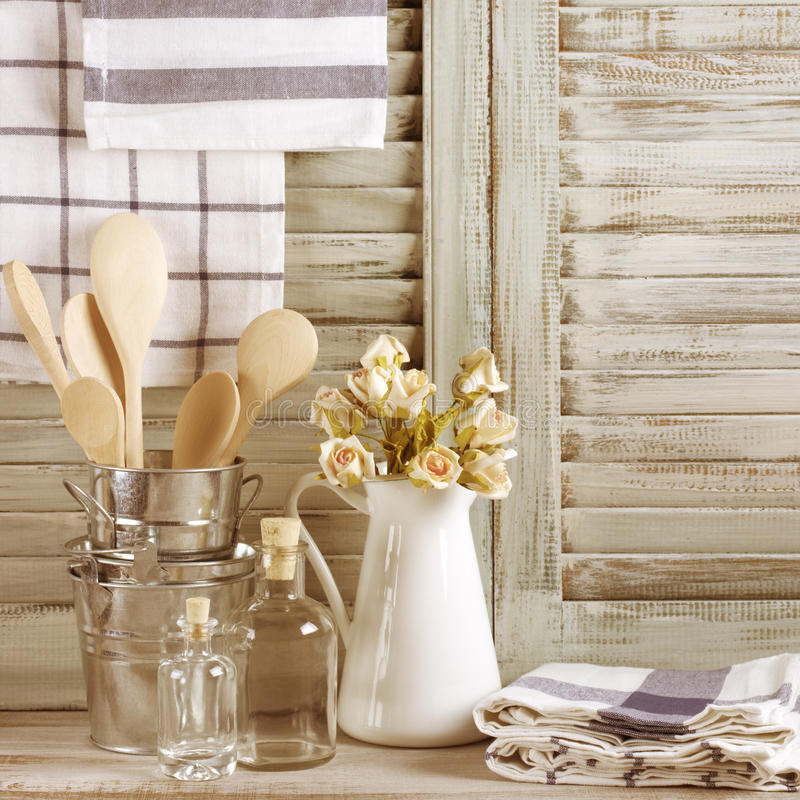 Rustic kitchen still life. White jug with roses bunch, galvanized buckets with wooden spoons, glass bottles and linen towels against vintage wooden shutters stock photo