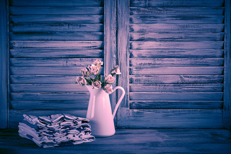 Rustic kitchen still life. White jug with roses bunch and towels stack against vintage wooden shutters. Strong filtered toned image stock images