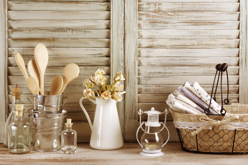 Rustic kitchen still life. Wire basket with towels stack, galvanized buckets with wooden spoons, jug with roses bunch, glass bottles and lantern against royalty free stock images