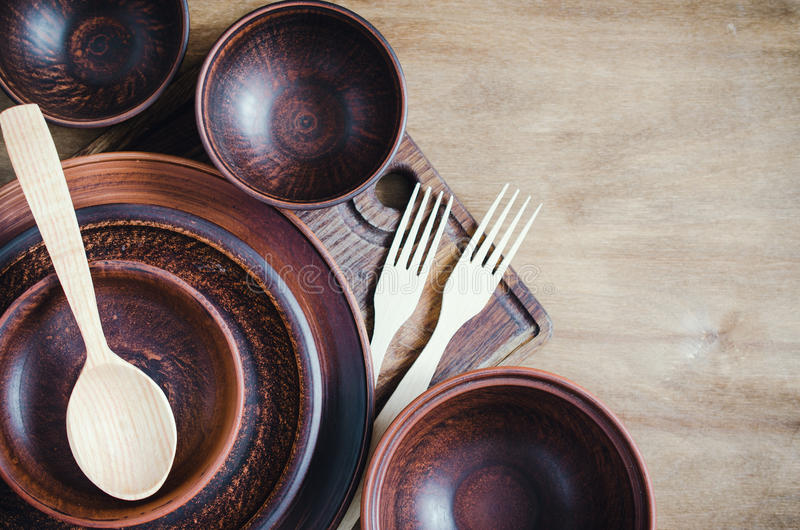 Rustic Kitchen Utensils. Home Wares. Rustic Kitchen Utensils: the Ceramic Plates and Wooden Cutlery on Wooden Background. Home Wares. Kitchen Decor in Rustic royalty free stock photos