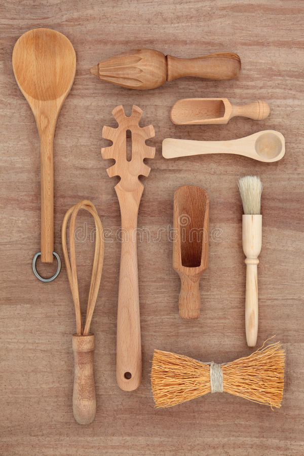 Rustic Kitchen Utensils. Wooden kitchen utensil selection over papyrus parchment background stock photos