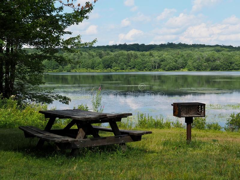 Lakeside Picnic Area With Barbeque. A rustic lakeside picnic area in the Pocono Mountains of Pennsylvania with green trees and clouds reflecting in water stock photos