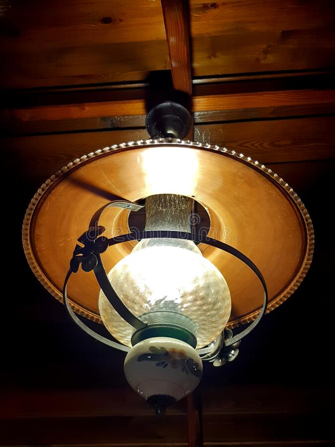 rustic lamp hanging from the wooden ceiling of the inn. metallic disc, glass and china bulb mounted in metal decorative frame. stock images