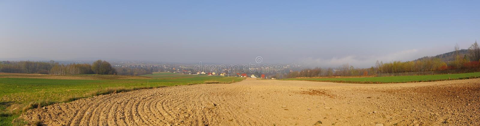 Rustic landscape with plowed field at spring stock photography