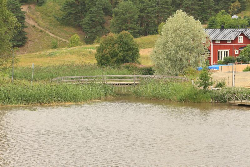 Rustic landscape. River, bridge and trees stock photo