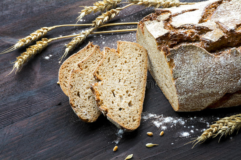 Rustic loaf of bread and slices with wheat on dark wood stock images