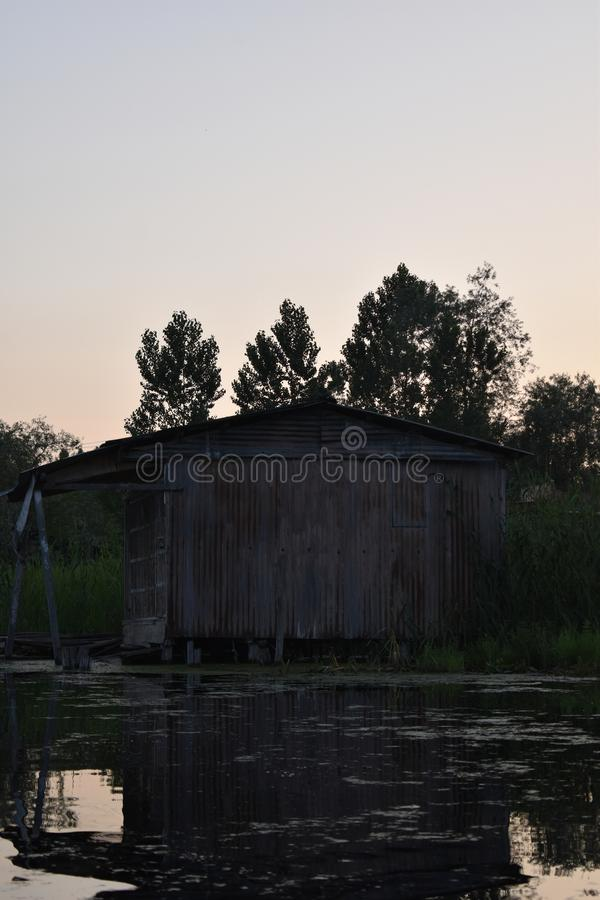 Rustic look of a old house made of tin with sunset sky background in the middle of Dal lake, Srinagar, Jammu and Kashmir, India. Water, reflection, reflections stock photography