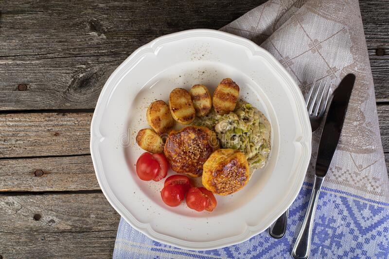 Rustic lunch. Lunch of fish cutlet with baby potatoes and leak sauce in a rustic setting stock image