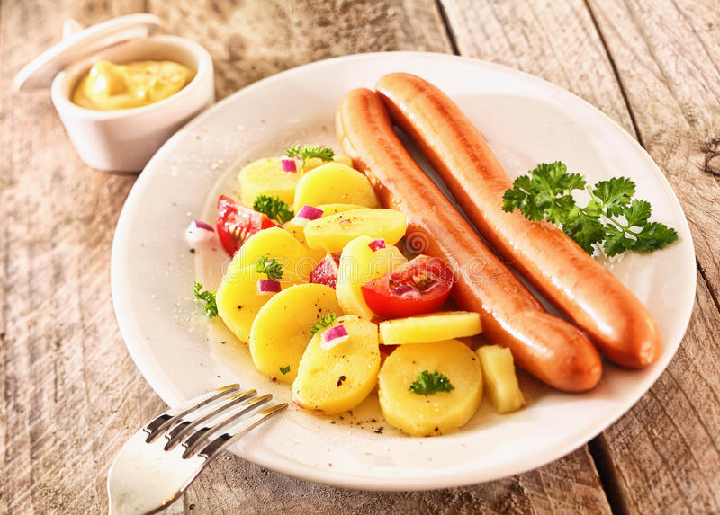Rustic lunch made of boiled potatoes and sausages. Tasty rustic lunch made of boiled potatoes and sausages, garnished with prasley, tomatoes, onion and mustard stock photography