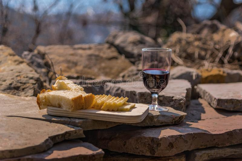 Rustic Lunch on the stone wall: homemade cheese, bread and wine. Mountain village. Reflection of the sky in wine. ecological tourism. Holy Trinity feast royalty free stock photos