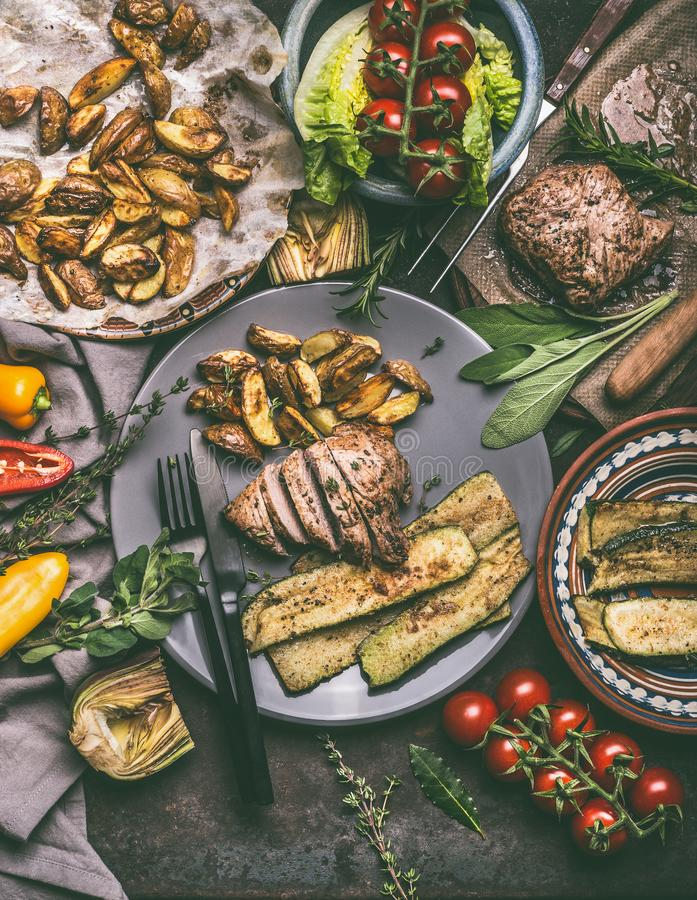 Rustic meal with roasted meat, baked potatoes and vegetables served on plate with cutlery. Top view stock images