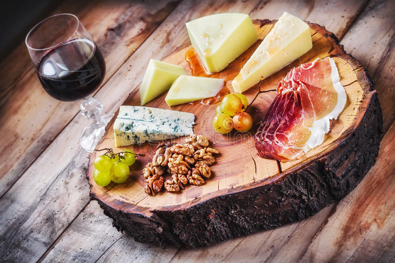 Rustic Mediterranean cheese board and a glass of red wine. Rustic Mediterranean cheese board with a glass of red wine royalty free stock photography
