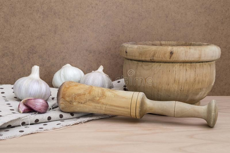 Rustic mortar to chop garlic on a wooden table. Kitchen mortar to crush food and garlic as a food condiment stock photography