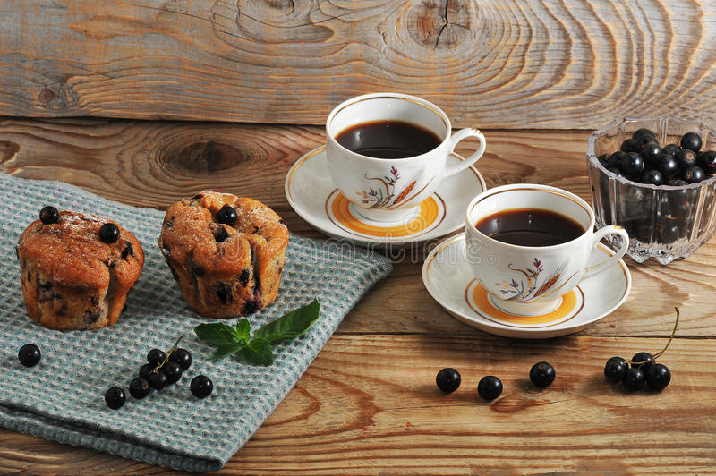 Rustic muffins with black currant and two cup of coffee. On wooden background stock image