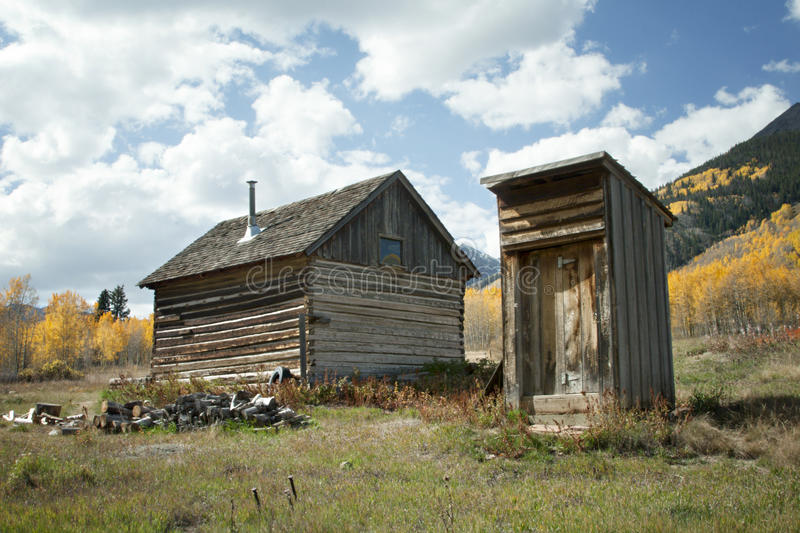 Rustic old cabin and outhouse in Fall Season