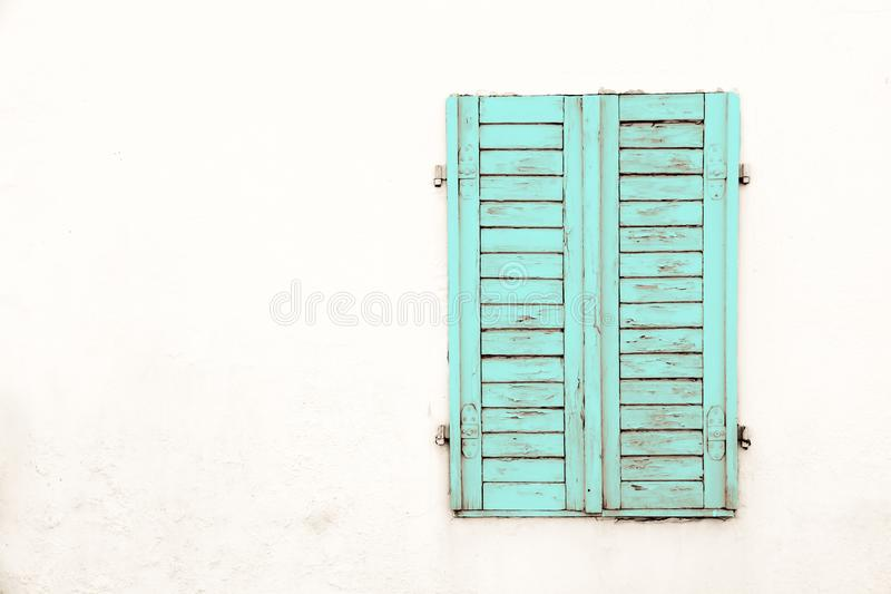 Rustic old grungy and weathered green cyan wooden closed window shutters with peeling paint stock image