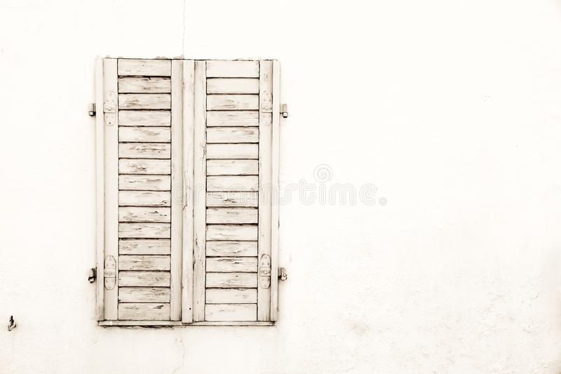 Rustic old grungy and weathered white grey wooden closed window shutters with peeling paint royalty free stock photo