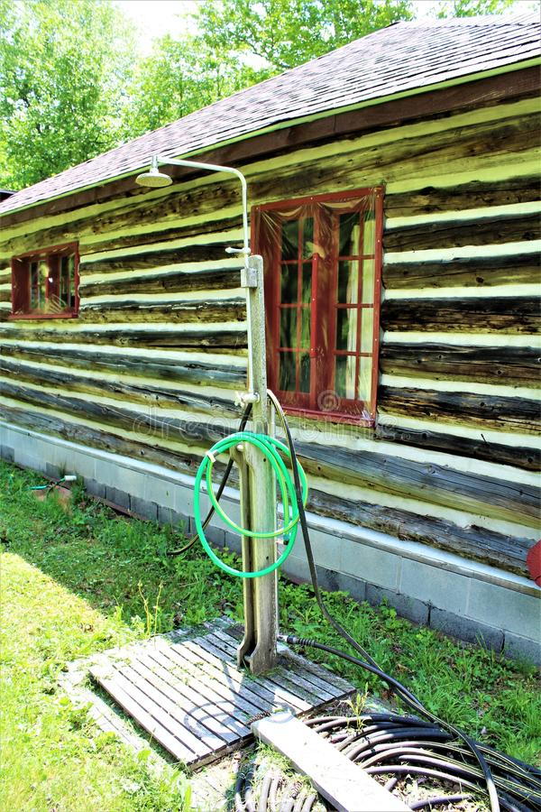 Rustic old log cabin outdoor shower located in Childwold, New York, United States. Rustic old traditional original log cabin outdoor shower located in Childwold stock image