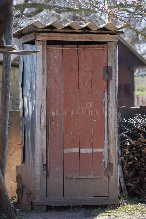 Rustic old times outdoor dry toilet in countryside. Spring landscape around stock photos