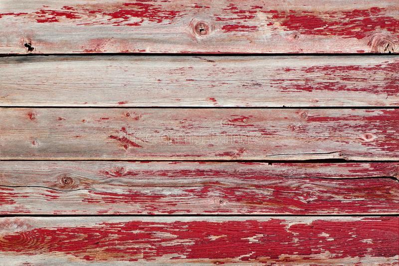 Rustic old weathered wood plank background with flaking red paint. Rustic old weathered wood background of planks with peeling red paint royalty free stock image