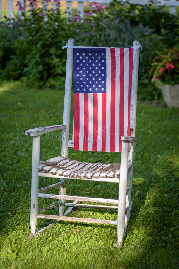 Rustic old white painted rocking chair sitting in lawn decorated royalty free stock photo