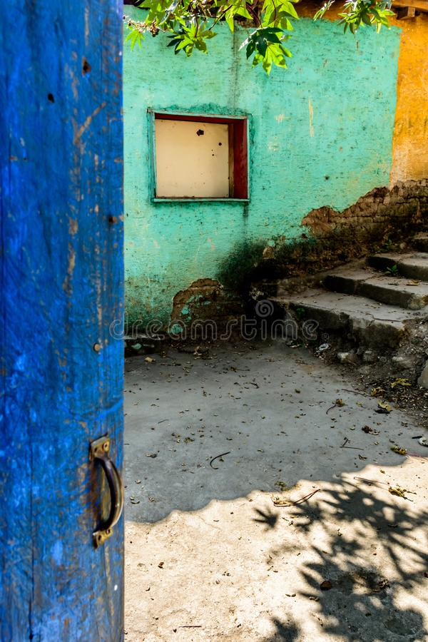 Rustic open blue door & turquoise & yellow wall. Rustic open blue painted door & turquoise & yellow building wall with boarded up window in Guatemala, Central stock photo
